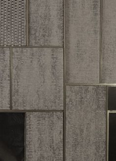 Dark handcut brick within meticulous metal frame, brick creates gaps, frame keeps it all rigid. structure is concrete frame internally.
