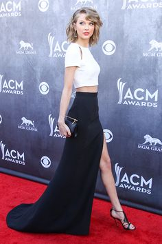TAYLOR SWIFT (2014 ACMs) / messy curls + cut-out, white crop-top + high-waisted thigh-high slit black maxi skirt w/train + snake cuff + black shoes w/metallic accents + matching black & metallic clutch.