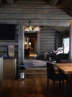 Husets planlösning är öppen och utrymmet väl tilltaget med 200 kvadratmeter boyta. Timmerstockar och annat nytt virke är betsade för att se gamla och lite väderbitna ut. Köksgolvet i förgrunden är lagt med gamla ekplankor, och bordet är, liksom mycket av inredningen, specialtillverkat. Taklampa från Blue nature.