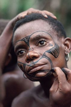 Africa |  An Efe Pygmy woman getting her traditional face painting done.  Image credit William (Bill) Wheeler.