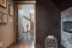 Leading into the master bedroom, a wood cladded wall and slate fireplace set an intimate ambiance.
