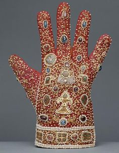 Die Handschuhe (Gloves - I love that the German for glove is 'hand shoe'!)  circa1220  Made of plain red samite, the gloves are densely decorated on the back. Golden tendrils embroidered in couched work fill the ground upon which enamel plaques, precious stones and pearls are mounted. On the back of each glove there is a central cloisonné appliqué in the shape of a palmette with a small pointed oval shield on either side with a bird's head above each of these. Between the heads, the...