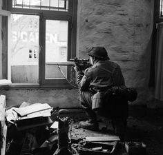 """A sniper from """"C"""" Company, 5th Battalion, The Black Watch , 51st (Highland) Division, in position in a ruined building in Gennep, Holland, 14 February 1945."""