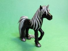 This little unicorn is made of high quality colored polymer clay, painted, and sealed with a glossy finish. He is solid black, with shimmery silver tail and mane. He is just under 3 inches tall and about 3 inches long.
