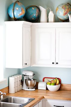 post has more photos... a pretty light and airy kitchen, love the combo of white cabinetry, dark hardware, light blue/green walls and wood countertops!