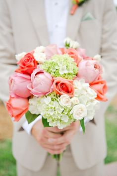 Coral and blush pink roses with creamy spray roses and green mini hydrangeas.