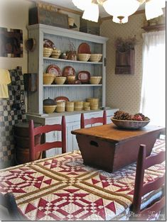 Prim Dining Room...love the quilt & box on the table and the yellow ware in the old blue cupboard... A Primitive Place ~ Tammy.