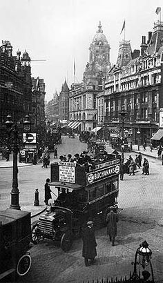 This street scene at the corner of Tottenham Court Road and Oxford Street shows an open-topped bus with bowler-hatted passengers. The YMCA building on the corner of Great Russell Street was erected in 1912 and replaced in the 1970s