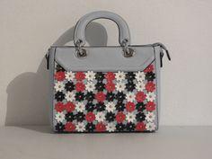 licht blauwe handtas met kleine witte, rode en zwarte bloemen.