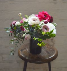 Flowers in recycled cut bottle vase. Ranunculus, thistle, peonies and mint. Tin Can Studios | Yelp