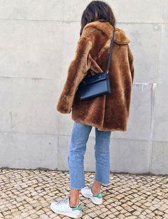 Fausse fourrure chocolat + jean coupé court sur la cheville + baskets blanches = le bon mix (photo Débora Rosa)
