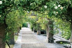 A herringbone brick path passes under a rose-covered pergola | archdigest.com