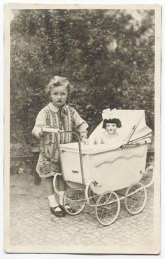 GIRL WITH DOLL IN BABY BUGGY.