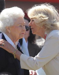 Camilla lays a hand on the Queen's shoulder as she greets her with a kiss