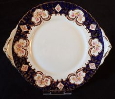 Beautiful cake plate with a scalloped rim decorated with a rich cobalt blue rim, floral motifs and hand painted gold scrolls and swags. This is a stylish piece for a special occasion or would look great in a display cabinet