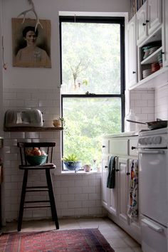 Rental kitchen brown cabinets painted white. Also new hardware, and subway tile!