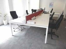 3 x 6-person Dynamobel white bench desks with red fabric dividing screen and cable tray under.
