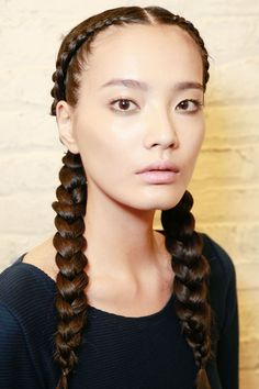Braids Are Back — And Cooler Than Ever #refinery29  Think pigtails can't be grown-up? Think again — the key to elevating the style, according to Esther Langham, who created the look for Beauty.com at the Kenneth Cole show, is creating a severe middle part and inside-out French braids (hint, weave strands under, rather than over, each other).