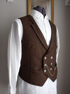 Fine double breasted waistcoat in Pure Wool Donegal Tweed in a rich earthy brown colour with a subtle herringbone weave. Features shawl collar, 2 hip pockets and 1 non-functioning breast pocket, pewter buttons and adjustable back belt. Fully lined in dark brown viscose. Fibre content: Outer 100% Wool Lining 100% Viscose Length approx. 23 (58cm) ONE ONLY available in chest size 42 (106.5cm DRY CLEAN ONLY