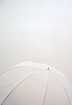 Armed with this pretty, white umbrella, we don't mind a bit of rain.