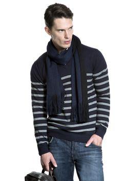 Tricô marinho listrado, cachecol dupla face petróleo e preto, calça jeans e mochila de nylon com couro. Produção perfeita para os finais de semana de meia-estação.