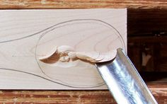 Push the gouge into the wood, working directly across the grain. Then move the handle laterally to make a slicing cut. It is best to remove wood from the center of the bowl first.