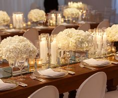 White floral centerpieces beautifuly pair with candles in clear hurricane holders.