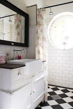Round window, flowered shower curtain, floor with black framed mirror.