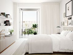 (Love the floor to ceiling curtains!) White and beige bedroom with a viewWhite and beige bedroom with a view