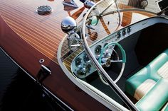 Beautiful wooden vintage boat. love the turquoise upholstery and steering wheel
