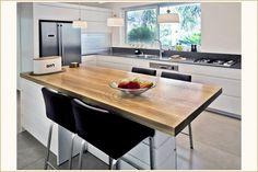 מטבח לבן מודרני בשילוב ידיות אינטגראליות ומגירות אינטיבו של בלום. במטבח יחידת אי המשלבת בוצר מאלון גושני ורגל מרכזית מודרנית כחלק אינטגרלי מהמטבח.