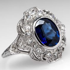 1920's Antique Blue Sapphire  Old Euro Cut Diamond Engagement Ring Platinum. This magnificent 1920's engagement ring features a bezel set beautiful natural sapphire at nearly 2 carats and a half a carat of high quality Old European cut diamond accents. This intricately detailed ring was crafted in solid platinum and is in good condition, especially considering the ring is nearly 100 years old.