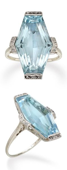 An Art Deco aquamarine and diamond ring, circa 1920. The lozenge-shaped faceted aquamarine weighing 10.96 carats, a row of four rose-cut diamonds set to each end and side, set to a platinum mount with ornate scroll pierced gallery, with fine tapered D-section platinum shank and cheniered shoulders.