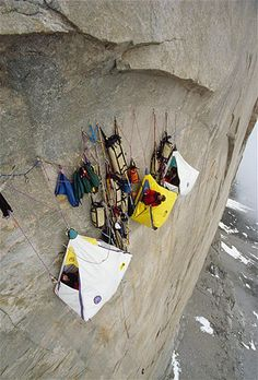 A group in Canada's Northwest Territories camps in portaledges protected from falling rock and ice by an overhang.Image: Camping in Canadas Northwest Territories (© National Geographic/Getty Images)