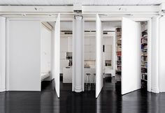 L'idea per questo loft è quella di poter circolare senza limitazioni e poi poterlo chiudere attraverso elementi free-standing mobili. Chiuso è un volume pulito che segue e include le colonne, aperto diventa cucina. A soffitto una struttura sostiene gli impianti (luce, aria, audio) e fa da supporto alle pareti pivotanti