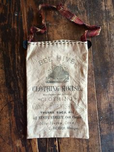 """Primitive 4 3/4"""" x 7 1/2"""" bag made from distressed muslin and printed with an advertisement for Bee Hive Clothing House. Comes with a homespun ribbon for hanging wherever. Black button and handquilted accents.  $6.95 Cdn plus shipping."""