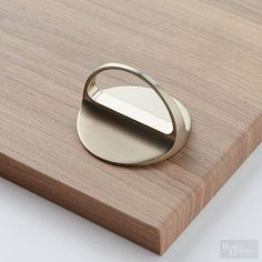 This round, low-profile blend between a knob and a pull mounts flat against cabinetry. The beautiful arched pull tab and smooth lines throughout create an upscale appearance./