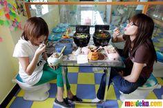 Dua pelanggan bersantap duduk di kursi toilet di sebuah restoran bernuansa serba toilet di Beijing China.