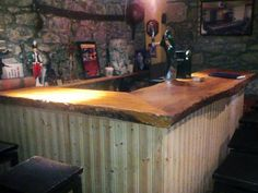 Rustic+basement+bar+with+stone+wall,+wood+countertop,+and+wood+plank+base.+