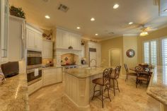 Traditional Kitchen with Breakfast bar, Custom hood, Kitchen island, Ceiling fan, Raised panel, Crown molding, Flush