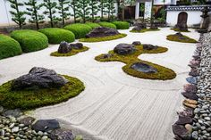 The rock garden at Myoren-ji, a Buddhist temple in Kyoto, features a traditional arrangement of stones, moss, and sand, while the perimeter includes rhododendrons and pine trees. The temple, destroyed twice by fires and reconstructed in its current incarnation in 1789, offers lodging for visitors year-round.