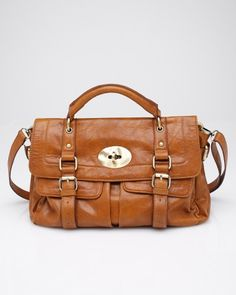 Maurissa  Fold over, turn lock boho style briefcase bag. Features faux buckle snap closure, two front snap pockets, inner utility and zip pockets, side buckle detail, adjustable and removable shoulder strap and top handle.