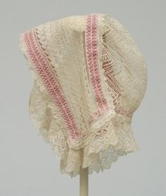 1830 cotton bonnet of very fine cream knitted lace with lace frill around short lappets and back. Decorated with two bands of pink cotton insides and with narrow band around back to hold garment in shape.