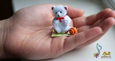 neli: White quilling teddy bear on a hand