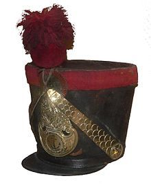 A shako (/ˈʃækoʊ/, /ˈʃeɪkoʊ/, or /ˈʃɑːkoʊ/) is a tall, cylindrical military cap, usually with a visor, and sometimes tapered at the top. It is usually adorned with some kind of ornamental plate or badge on the front, metallic or otherwise, and often has a feather, plume (see hackle), or pompom attached at the top.