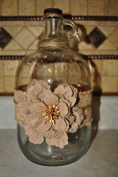 moon shine jug with burlap trim and twine wrapped around the top.