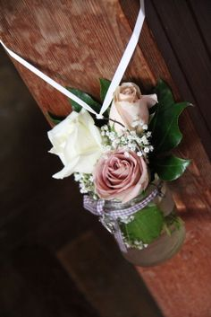Posies of fresh Roses and Gypsophilia in Jam Jars were hanging on the ends of the Pews