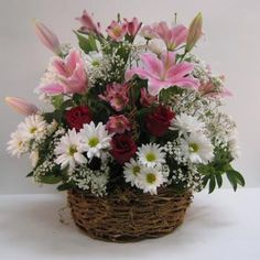 Roses, Stargazer Lilies, white daisies and pink alstroemeria with babies breath in a natural grapevine basket. A lovely expression of sympathy especially suitable for a woman.