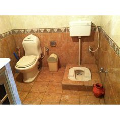 Two toilets in a middle-class Pakistani home, 2012.  One commode and one Persian-style squat toilet. Red pitcher on right is for washing oneself.  On left the commode has a sprayer.