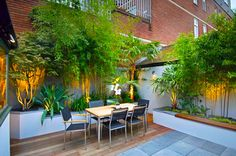 Small urban garden showing a contrast of textures between the paving and the decking, adding a modern touch. The uplighting on the planting also makes this area suitable for after dark entertaining.